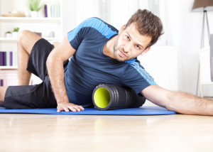 Gorgeous Athletic Young Guy Using Foam Roller in Doing an Indoor Exercise While Looking at You.