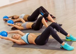 Three attractive sport girls smiling while working out with fitness ball lying on yoga mat in fitness class