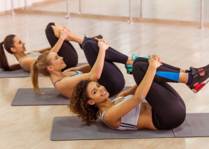 Three attractive sport girls smiling while working out lying on yoga mat in fitness class. Beautiful Afro-American girl looking at camera
