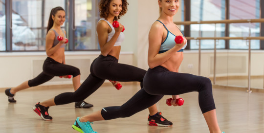 Three attractive sport girls smiling while working out with dumbbells and doing lunges in fitness class