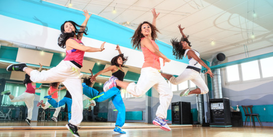 group of  women in sport dress at fitness dance exercise or aerobics