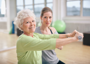 Senior woman exercising with fitness trainer at gym. Active senior woman lifting dumbbells with help from personal trainer.