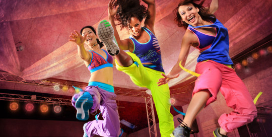 young women in sport dress jumping at an aerobic and zumba exercise