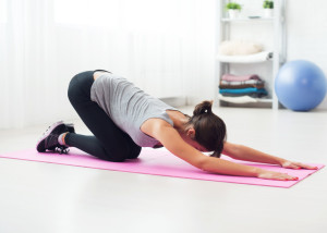 fit woman bending over on mat doing pilates exercise at home in the living room.