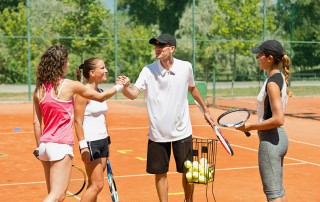 Popular tennis instructor surrounded with students, training starts